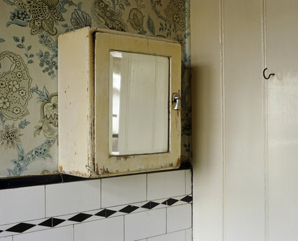 Worn bathroom cabinet with a mirror on the front in the bathroom of John Lennon's boyhood home, Mendips, in Liverpool