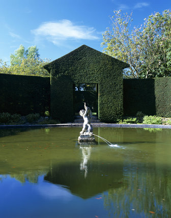 The Bathing Pool Garden at Hidcote, with the Boy Fountain in the middle of the pool, and surrounded by strict topiary clipped into the shape of an entry archway