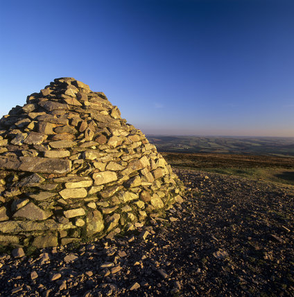 The stone cairn on the summit of Dunkery Beacon on the Holnicote Estate with a view of the countryside behind