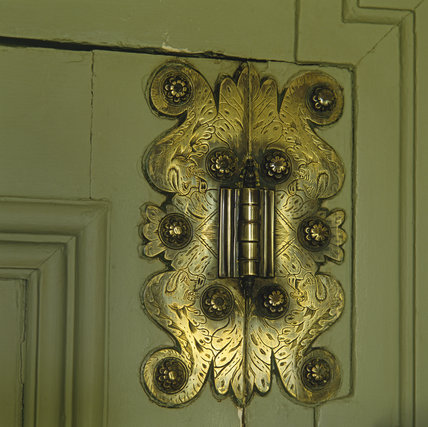 Detail of a door hinge in the Tea-Rooms at Nunnington Hall, showing intricate engraving and flower nail-heads