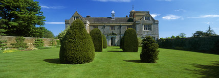 The southern aspect of Canons Ashby House, viewed down an avenue of yew topiary