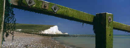 The Seven Sisters seen beyond the shingle beach and framed by the timbers of a breakwater