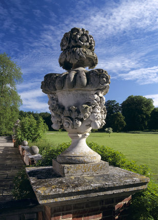 An elaborately swagged limestone urn, dating from the C18th