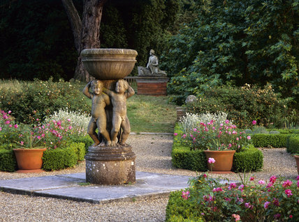 Putti supporting a bowl in the Jeykll garden at Hatchlands A statue of