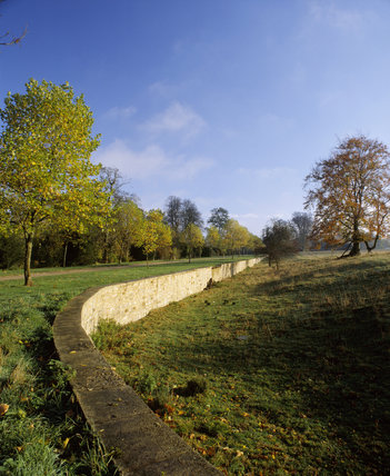 The stone Ha-ha at Stowe Landscape Gardens, running from the foreground into the distance, with autumnal trees each side