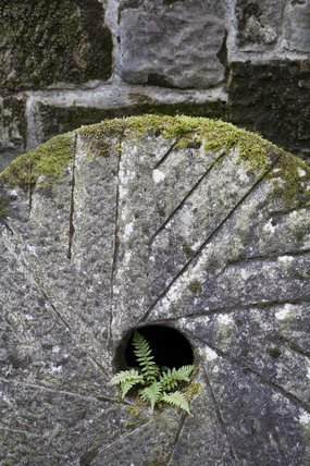 Close up of an old millstone at Stainsby Mill, a working, water-powered flour mill on the  Hardwick Hall Estate, Derbyshire