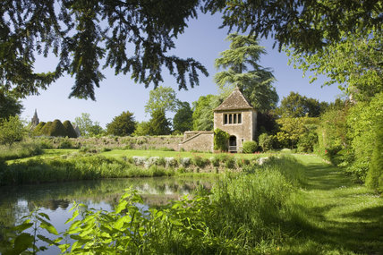 The Apple House, seen across the moat or stewpond in the gardens at the fifteenth-century Great Chalfield Manor, Wiltshire