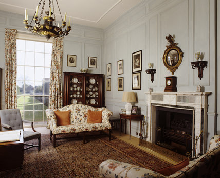 The Library at Hanbury Hall, Worcestershire, looking towards the fireplace and window including the Regency bookcase displaying ceramics and the Regency ormolu chandelier, originally intended to burn colza oil