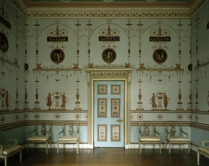 A wall of the Etruscan Dressing Room at Osterley, decorated like a neo-classical print room and painted with maidens dancing round tripods which are framed within arabesque arches