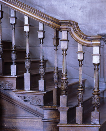 Detail of the carved oak balusters and tread ends at the foot of the Painted Staircase in the Hall at Hanbury Hall, Worcestershire