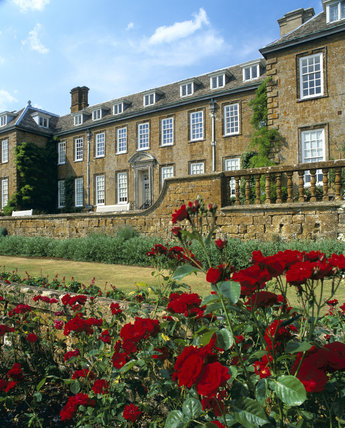 The double terrace and balustrade on the South or garden side of Upton House, Warwickshire with the bright red of Rosa