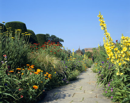 The borders planted with hot summer colours in yellow and orange along the raised Terrace Walk at Packwood House, Warwickshire