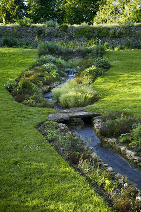 Stream planted along its banks in the garden at Great Chalfield Manor, Wiltshire