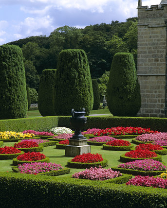 The parterre at Lanhydrock with beds of colourful annuals edged by box with an urn in the centre