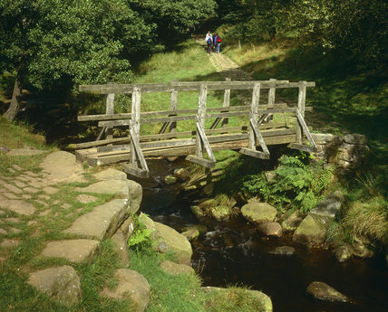 Medium view of a wooden bridge over Burbage Brook on Longshaw estate showing stone boulders edging the approach and a stony path above surrounded by trees with visitors walking in sunshine