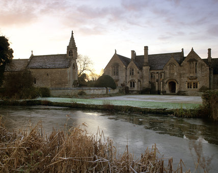 Great Chalfield Manor, viewed across the frozen moat, with frost dusting the grass