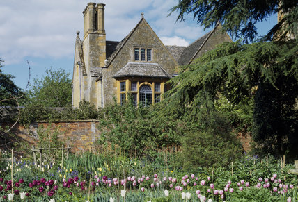 View of Hidcote Manor from The Old Garden in May with tulips in the foreground