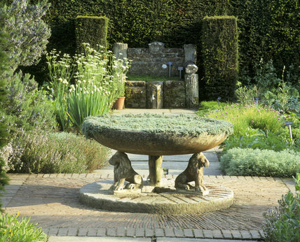The Herb Garden at Sissinghurst Castle Garden, showing the central stone bowl with lion carved leg supports, and stone trough in the hedge in the background