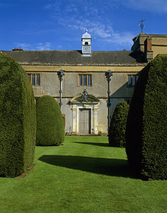 The west front of Canons Ashby, with yew topiary leading up to the door