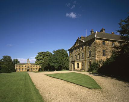 Oblique view of the Entrance Front to the mid-C18th house with the stable block in the background