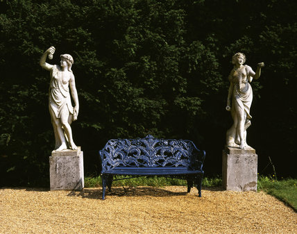 Two statues flank an iron seat, on the Terrace at Hughenden Manor