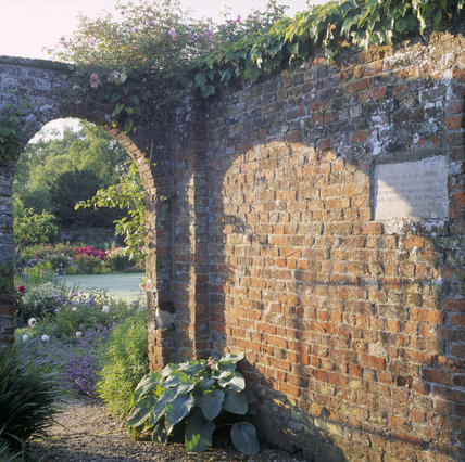 View through the arch of the old red-brick wall in the garden at Gunby Hall, showing the quotation by Rudyard Kipling carved in stone and set into the wall to the right of the photograph