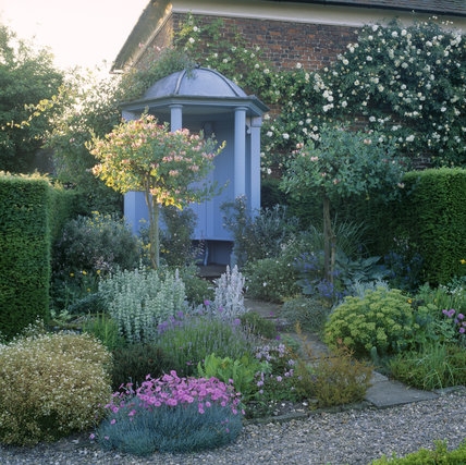 View of the abundant flowers and plants surrounding a pale blue, ornamental, temple-like structure in the garden at Gunby Hall, taken in late afternoon light