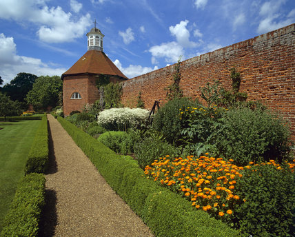 Looking down the box lined gravel path to the working Dovecote at Felbrigg Hall in July