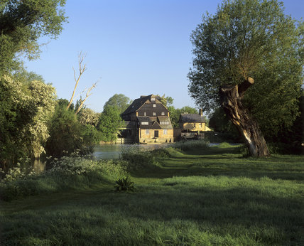 A distant view of Houghton Mill, a large timber-built watermill, on an island, in the Great Ouse