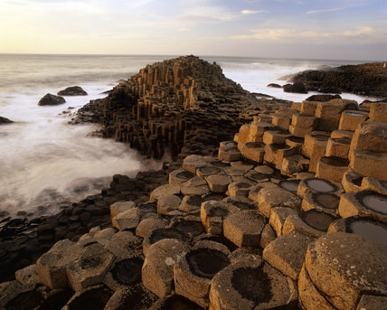 A coastal view taken at the Giant's Causeway, with the sea in motion and the unusual rock formations towered up in the foreground