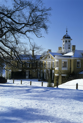 View across a snow covered field towards the house at Polesden Lacey