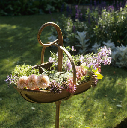 An ornamental display of cut flowers arranged in a wooden trug mounted on a shepherd's crook type pole, in the garden at Peckover House