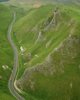 A view of the road through Winnat's Pass, the deep rugged gorge through the landscape of Mam Tor in the Peak District, Derbyshire