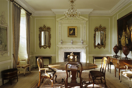 The Dining Room at Peckover House showing the C18th dining table and chairs and a two-tier chimneypiece set into the panelling from the same date