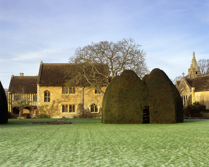 An unusual yew tree house with Great Chalfield Manor in the background