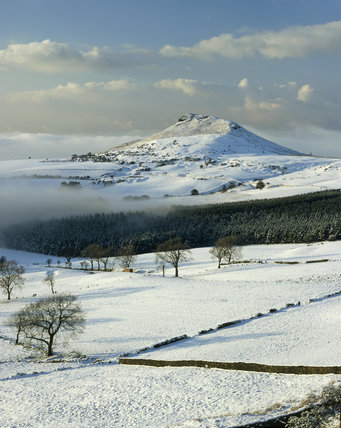 The snow covered peak of Roseberry Topping, viewed across the misty fields