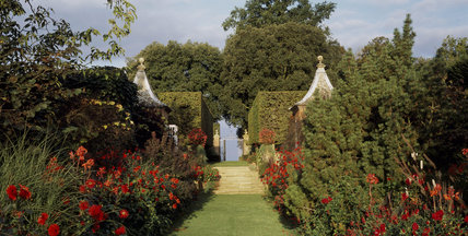 Panoramic view of The Red Borders leading up to the Pavilions and the gateway to The Stilt Garden in the morning light at Hidcote Manor