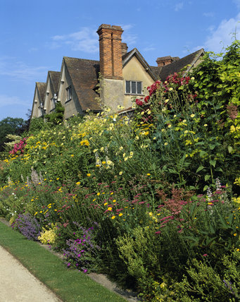 Summer border at Packwood House, Warwickshire, with a glimpse of the house beyond