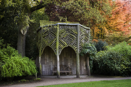 The Bark House, a rustically styled seating arbour, in the garden at Dunham Massey, Cheshire