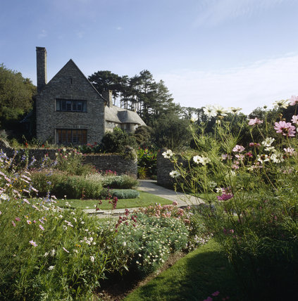 Pretty planting in the garden with exterior of Coleton Fishacre beyond, the Arts & Crafts-style house designed in 1925 for Rupert and Lady Dorothy D'Oyly Carte, at Kingswear, Devon