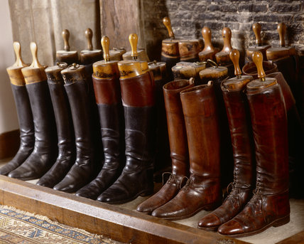 Leather boots lined up in the fireplace of the front stairs at Great Chalfield Manor, near Melksham, Wiltshire