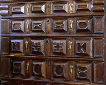 Close view of the carved wooden chest in the North Bedroom at Great Chalfield Manor, near Melksham, Wiltshire