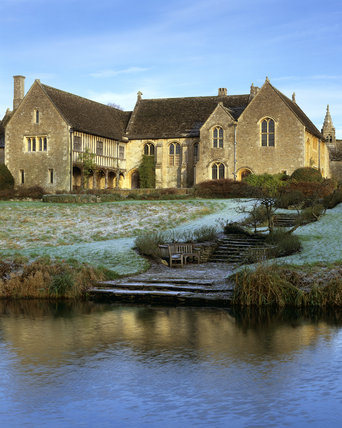 Great Chalfield Manor with steps leading down to the part frozen moat
