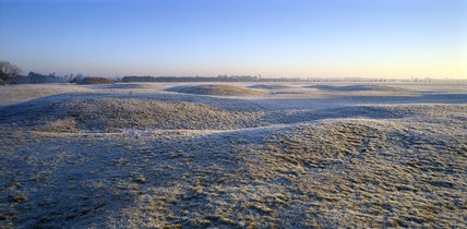 A view across the frost covered burial mounds at Sutton Hoo on a frosty dawn morning