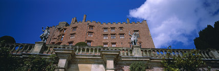 A view looking up towards Powis Castle against a blue sky on a sunny day
