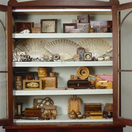 Detail of a display cabinet containing a collection of marquetry boxes, fans, opera glasses & bottles, in the P
