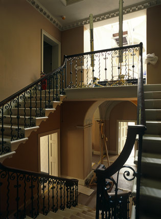 View from the top of the double staircase at Llanerchaeron down into the front hall, showing wrought iron banisters, a panelled door and an archway, during restoration