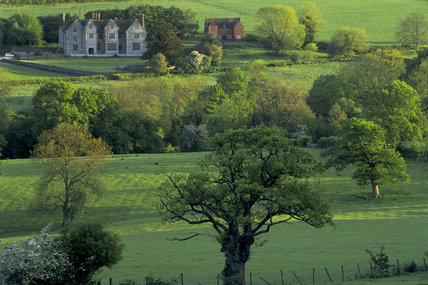 A view across the countryside to Wilderhope Manor; the house was built of limestone c.1586 and unaltered with C17th plaster ceilings, it was given to the National Trust in 1936.
