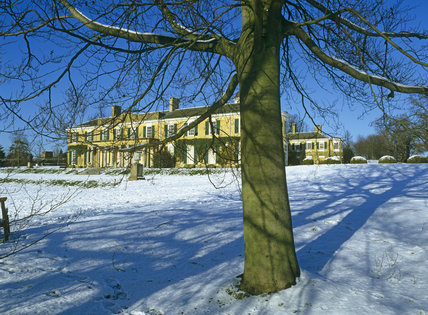 The low winter sun catching the south front of the House as seen across the snow covered ground