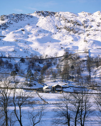 The two buildings, known as St.Anne's Studio and Chapel Stile, surrounded by snow covered fields with the ground rising up behind, in a dazzling white backcloth.